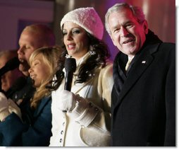 """President George W. Bush joins Sara Evans in singing """"We Wish you a Merry Christmas"""" on stage at the Ellipse Thursday, Dec. 6, 2007, during the festivities surround the lighting of the National Christmas Tree. White House photo by Shealah Craighead"""