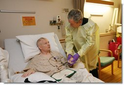 President George W. Bush visits with U.S. Army Capt. Patrick J. Horan of West Springfield, Va., at the National Naval Medical Center in Bethesda, Md., Wednesday, Dec. 19, 2007, after awarding Horan a Purple Heart medal and citation. Captain Horan is recovering from a head injury sustained in Operation Iraqi Freedom. White House photo by Joyce N. Boghosian