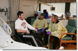 President George W. Bush sits and visits with U.S. Marine Lance Cpl. Michael Stilson of Clarkson, W. Va., and his father, Robert Stilson, at the National Naval Medical Center in Bethesda, Md., Wednesday, Dec. 19, 2007. Stilson is recovering from injuries sustained in Operation Iraqi Freedom. White House photo by Joyce N. Boghosian