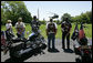 Members of the motorcycle group Rolling Thunder watch President George W. Bush and First Lady Laura Bush land on the South Lawn of the White House from a visit to Camp David. White House photo by Chris Greenberg