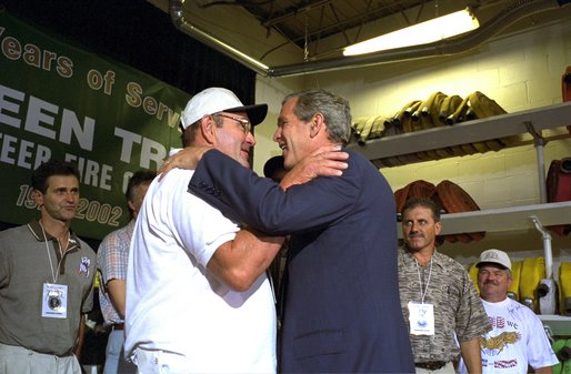President George W. Bush embraces rescued coal miner John Unger at the Green Tree Fire Department in Green Tree, Pa., Monday, Aug. 5. Pulled from a collapsed mine in Somerset, Pa., nine miners survived three days in a flooded mine shaft before rescuers found them. Also pictured are, from left to right, miners Mark Popernack, Randy Fogle and Tom Foy. White House photo by Paul Morse. White House photo by Paul Morse.