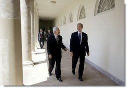 President George W. Bush and Palestinian Prime Minister Mahmoud Abbas walk along the colonnade after their joint press conference in the Rose Garden Friday, July 25, 2003. Meeting for the first time at the White House, the two leaders held a working lunch and a meeting in the Oval Office.  White House photo by Paul Morse