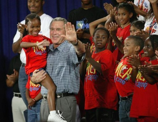 President George W. Bush joins children from Lakewest Family YMCA on stage after speaking on his Health and Fitness Initiative in Dallas, Texas, Friday, July 18, 2003. White House photo by Eric Draper