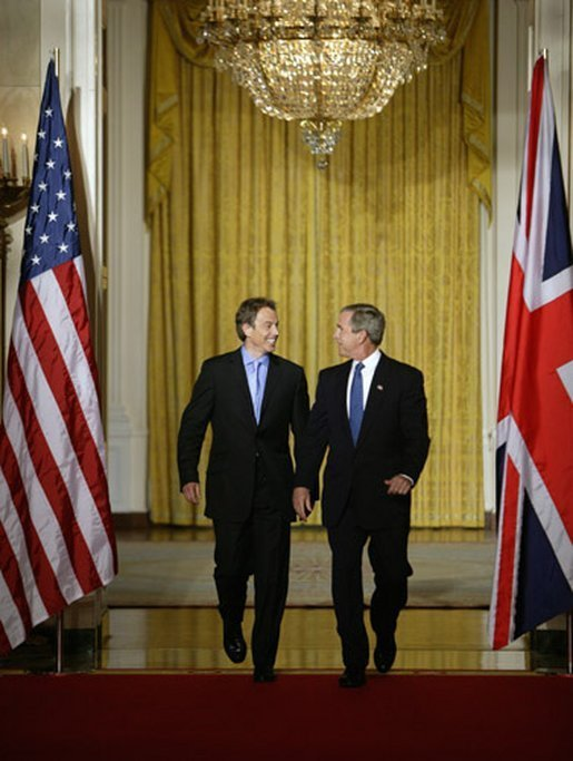 President George W. Bush and British Prime Minister Tony Blair walk through the Cross Hall of the White House before the start of their news conference, Thursday, July 17, 2003. White House photo by Paul Morse