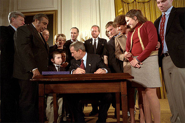 """President George W. Bush looks over to Thomas Martello, 6, during the signing ceremony of the Victims of Terrorism Tax Relief Act in the East Room Jan. 23. """"We're joined today by families who have lost loved ones in the great acts of evil,"""" said the President. """"As you draw on faith and personal strength to cope with your grief, I hope you'll also find comfort in the knowledge that your nation stands with you and prays for you. We mourn those whom we've lost, and we face the future together."""" White House photo by Eric Draper."""