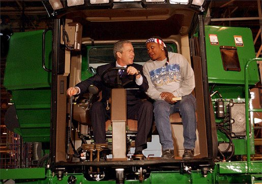 """President George W. Bush talks with assembly worker Deborah Davis after starting up a combine with a gold-plated ignition key at John Deere Harvester Works in East Moline, Ill., Monday, Jan. 14, 2002. """"I'm confident in the American farmer,"""" said the President, addressing about 1500 employees and supporters. """"I know the American farmer is more efficient, and can raise more crop than anybody, anywhere in the world."""" White House photo by Eric Draper."""