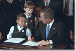 """With the help from some new friends, President George W. Bush signs legislation promoting safe and stable families at the White House Jan. 17, 2002. """"The legislation reaffirms our country's commitment to helping children grow up in secure and loving families by encouraging adoption,"""" said the President during the ceremony. White House photo by Paul Morse."""