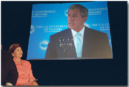 Laura Bush looks on in the audience as President George W. Bush is displayed on a giant screen monitor during his speech at the 69th Conference of Mayors in Detroit, Michigan, Monday, June 25, 2001. White House photo by Eric Draper.