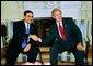 El Presidente George W. Bush se reúne con el Presidente Antonio Saca de El Salvador en la Oficina Oval el Lunes, 12 de julio de 2004. White House photo by Eric Draper