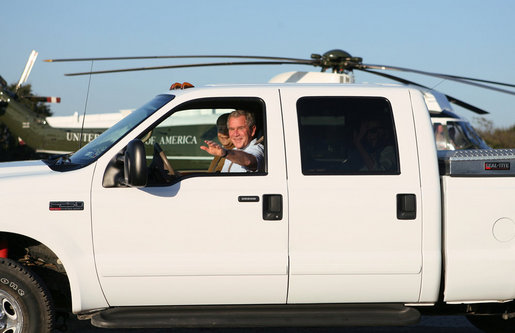 President George W. Bush waves as he drives German Chancellor Angela Merkel, Mrs. Laura Bush and Merkel's husband, Dr. Joachim Sauer, following the Merkel's arrival to the Bush ranch in Crawford, Texas, Friday, Nov. 9, 2007. White House photo by Shealah Craighead