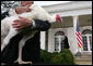 """President George W. Bush waves farewell to invited guests as a grateful """"Flyer"""" the turkey watches Wednesday, Nov. 22, 2006 from the White House Rose Garden, following the President's pardoning of the turkey before the Thanksgiving holiday. White House photo by Paul Morse"""