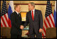 """President George W. Bush and President Vladimir Putin of Russia exchange handshakes Sunday, Nov. 19, 2006, at the Sheraton Hanoi after their two countries signed agreements supporting Russia's accession into the World Trade Organization. Said President Bush afterward, """"This is a good agreement for the United States. And it's an equally important agreement for Russia. And it's a good agreement for the international trading community."""" White House photo by Eric Draper"""