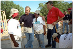 """President Bush and Secretary for Housing and Urban Development Martinez, far right, talk with new friends during a break from their house-building efforts at the Waco, Texas, location of Habitat for Humanity's """"World Leaders Build"""" construction drive August 8, 2001. White House photo by Eric Draper."""