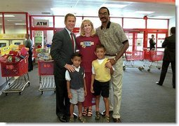 After talking with several families about how far $600 can go during family shopping trips, President Bush poses for pictures with one of the families just outside the Target Snack Bar at a retail location in Kansas City, Mo., Aug. 21, 2001.  White House photo by Moreen Ishikawa