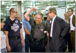 Showing off a little motor muscle, employees at Harley Davidson took turns showing President Bush around their Milwaukee factory during a visit Aug. 20. White House photo by Moreen Ishikawa.