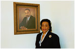 Coretta Scott King poses next to the portrait of her late husband, Dr. Martin Luther King, in the East Colonnade of the White House in Feb. 25, 2004.