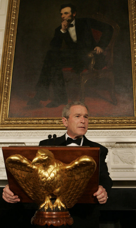 President George W. Bush, standing beneath a painting of President Abraham Lincoln, Sunday evening, Feb. 26, 2006 in the State Dining Room of the White House, welcomes guests to the State Dinner for the nation's governors. White House photo by Kimberlee Hewitt