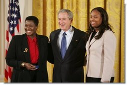 President George W. Bush is joined by Joan Thomas of Smyrna, Ga., left, and Erica Turner, who was mentored by Thomas, after Thomas received the President's Volunteer Service Award at a White House celebration of African American History Month.  White House photo by Paul Morse