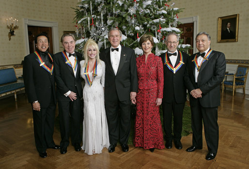 """President George W. Bush and Mrs. Laura Bush stand with the Kennedy Center honorees in the Blue Room of the White House during a reception Sunday, Dec. 3, 2006. From left, they are: singer and songwriter William """"Smokey"""" Robinson; musical theater composer Andrew Lloyd Webber; country singer Dolly Parton; film director Steven Spielberg; and conductor Zubin Mehta. White House photo by Eric Draper"""