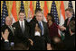 President George W. Bush acknowledges the applause of invited guests after signing H.R. 5682 The United States-India Peaceful Atomic Cooperation Act, Monday, Dec. 18, 2006, in the East Room of the White House. H.R. 5682 will allow the U.S. and India to share civilian nuclear technology and bring India's civilian nuclear program under the safeguards of the International Atomic Energy Agency. White House photo by Kimberlee Hewitt