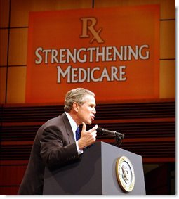 """President George W. Bush addresses the audience at Devos Performance Hall in Grand Rapids, Mich., Wednesday, Jan. 29, 2003. """"I urged the Congress last night to put aside all the politics and to make sure the Medicare system fulfills its promise to our seniors,"""" President Bush said. """"I believe that seniors, if they're happy with the current Medicare system, should stay on the current Medicare system. That makes sense. If you like the way things are, you shouldn't change. However, Medicare must be more flexible. Medicare must include prescription drugs.""""  White House photo by Tina Hager"""