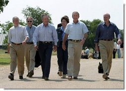 After talking with the press, President George W. Bush walks with his economic advisorsat his ranchin Crawford, Texas, Wednesday, August 13, 2003. Pictured are, from left,Director of the Office of Management and Budget Josh Bolten, Assistant to the President for Economic Policy Stephen Friedman, Secretary of Commerce Don Evans, Secretary of Labor Elaine Chao and Secretary of the Treasury John Snow.  White House photo by Susan Sterner