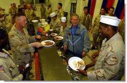 President George W. Bush meets with troops and serves Thanksgiving Dinner at the Bob Hope Dining Facility, Baghdad International Airport, Iraq,, Thursday, November 27, 2003.  White House photo by Tina Hager
