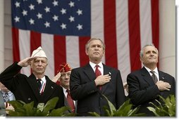 "President George W. Bush stands with National Commander of the Army and Navy Union David Berger, left, and Secretary of Veterans Affairs Anthony Principi during the Veterans Day ceremonies at Arlington National Cemetery Tuesday, Nov. 11, 2003. ""We observe Veterans Day on an anniversary -- not of a great battle or of the beginning of a war, but of a day when war ended and our nation was again at peace,"" said the President. ""Ever since the Armistice of November the 11th, 1918, this has been a day to remember our debt to all who have worn the uniform of the United States.""  White House photo by Paul Morse"