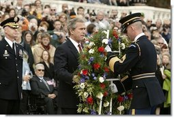 "Honoring those who died in service to America, President George W. Bush lays a wreath at the Tomb of the Unknowns in Arlington Cemetery on Veterans Day Nov. 11, 2003. After the wreath was placed, ""Taps"" was played and a moment of silence was observed.  White House photo by Paul Morse"