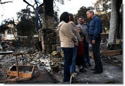 President George W. Bush meets with the Bentley family during a walking tour of the fire-damaged Harbison Canyon community in San Diego, Calif., Tuesday, Nov. 4, 2003. The Bentley family lost their home in last week's wildfires.  White House photo by Eric Draper
