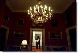 Viewed from the Red Room, President George W. Bush addresses the nation from the Cross Hall in the White House Monday evening, March 17, 2003.  White House photo by Eric Draper