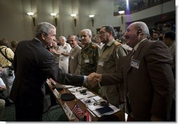 President George W. Bush reaches out to Mr. Shahib Hamad Adnan, Director of Policy and Requirements for the Iraq Defense Department, after delivering remarks Tuesday, May 1, 2007, to the CENTCOM Coalition Conference at MacDill Air Force Base in Tampa. With them are, from left: Mr. Mowaffak Al Rubaie, Iraqi National Security Advisor; Lt. General Yacoob Abdul-rizzaq, Deputy Chief of Staff for Iraq Joint Forces; and Major General Abdul Hasan Mohsen, Director General of Directorate of Border Enforcement.  White House photo by Eric Draper