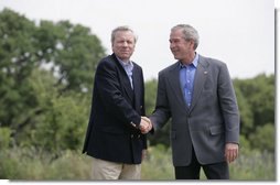 """President George W. Bush shakes hands with NATO Secretary General Jaap de Hoop Scheffer Monday, May 21, 2007, as the two wound up a visit to the Bush Ranch in Crawford, Texas. The President thanked the Secretary-General for his leadership and called him a """"strong advocate of fighting terror, spreading freedom, helping the oppressed and modernizing this important alliance."""" White House photo by Shealah Craighead"""