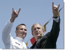 President George W. Bush and U.S. Coast Guard graduate Brian Robert Staudt offer the Texas Longhorns hand sign out to the audience following the President's address to the graduates Wednesday, May 23, 2007, at the U.S. Coast Guard Academy commencement in New London, Conn. White House photo by Joyce N. Boghosian
