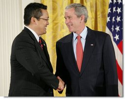 President George W. Bush shakes hands with Kay Hiramine of Colorado Springs, Colo., as he presents Hiramine with the President's Volunteer Service Award Thursday, May 10, 2007, in the East Room of the White House, in celebration of Asian Pacific American Heritage Month.  White House photo by Eric Draper