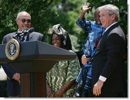 """President George W. Bush holds Baron Mosima Loyiso Tantoh in the Rose Garden of the White House Wednesday, May 30, 2007, after delivering a statement on PEPFAR, the President's Emergency Plan for AIDS Relief. With them are the boy's mother, Kunene Tantoh, representing Mothers to Mothers, which provides treatment and support services for HIV-positive mothers in South Africa, and Dr. Jean """"Bill"""" Pape, internationally recognized for his work with infectious diseases.  White House photo by Chris Greenberg"""