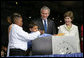President George W. Bush and Mrs. Laura Bush have a little help onstage Sunday, May 13, 2007, placing items in a time capsule during the 400th anniversary celebration of Jamestown. White House photo by Eric Draper