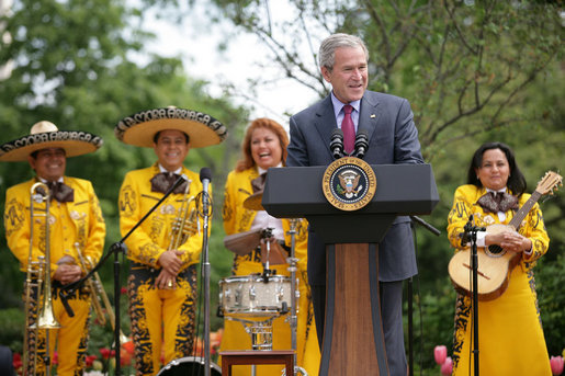 President George W. Bush welcomes guests to the Rose Garden at the White House Friday, May 4, 2007, to celebrate Cinco de Mayo and recognize the contributions of Mexican Americans. Members of the band Los Hermanos Mora Arriaga, who performed at the ceremony, are seen in background. White House photo by Eric Draper