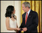 President George W. Bush congratulates Angela An of Washington, D.C., on presenting her the President's Volunteer Service Award Thursday, May 10, 2007, in the East Room of the White House, in celebration of Asian Pacific American Heritage Month. White House photo by Eric Draper