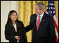 President George W. Bush congratulates Anna DeSanctis of Houston, Texas, after presenting her with the President's Volunteer Service Award Thursday, May 10, 2007, in the East Room of the White House, celebrating Asian Pacific American Heritage Month. White House photo by Eric Draper