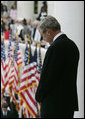 """President George W. Bush bows his head during the reading of the invocation at the Memorial Day ceremony Monday, May 28, 2007, at Arlington National Cemetery in Arlington, Va. Addressing the gathered audience President Bush said, """"The greatest memorial to our fallen troops cannot be found in the words we say or the places we gather. The more lasting tribute is all around us—a country where citizens have the right to worship as they want, to march for what they believe, and to say what they think."""" White House photo by Joyce Boghosian"""