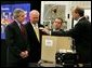 """President George W. Bush looks at a prototype for a fuel cell auxiliary power unit for the Bradley A3 fighting vehicle during a tour of the technology company, """"Battelle,"""" with Energy Secretary Sam Bodman, left, vice president Bill Madia, center, and vice president Henry Cialone in Columbus, Ohio, Wednesday, March 9, 2005. White House photo by Krisanne Johnson"""