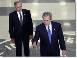 Central Intelligence Agency Director Porter Goss listens as President Bush delivers a brief statement to the media after visiting with CIA employees at their headquarters Thursday, March 3, 2005, in Langley, Va.  White House photo by Paul Morse