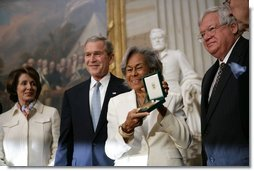 Rachel Robinson accepts the Congressional Gold Medal on behalf of her husband Jackie Robinson during a ceremony at the U.S. Capitol, Wednesday, March 2, 2005. Pictured, from left, are Congressional Minority Leader Nancy Pelosi, President George W. Bush, Rachel Robinson and Speaker of the House Dennis Hastert.  White House photo by Eric Draper