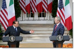 President George W. Bush listens as Italian Prime Minister Silvio Berlusconi addresses his remarks at a joint press availability Monday, Oct. 13, 2008, in the White House Rose Garden. Prime Minister Berlusconi said that Italy and America share a special friendship which has its roots in common values, in sharing a world which is inspired by love for democracy and freedom. White House photo by Chris Greenberg