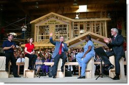 President George W. Bush acknowledges the audience at the conclusion of a conversation on homeownership at the Carpenters Training Center in Phoenix, Ariz., Friday, March 26, 2004. Pictured on stage with the President, from left, are construction foreman Jorge Sotelo, first-time homebuyer Emily McElhaney, first-time homebuyer Monica Sims and Doug McCarron, General President of the United Brotherhood of Carpenters and Joiners of America. White House photo by Eric Draper