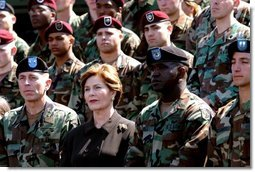 """Laura Bush listens while President George W. Bush delivers his remarks at Fort Campbell, Ky., Thursday, March 18, 2004. """"Since we last met, you helped to build medical clinics and to rebuild schools. By your decency and compassion, you are helping the Iraqi people to reclaim their country. Because you care, you're helping the Iraqis live as free people,"""" said the President.  White House photo by Tina Hager"""