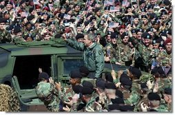 """President George W. Bush and Laura Bush are welcomed by military personnel, including the 101st Airborne Division, at Fort Campbell, Ky., Thursday, March 18, 2004. """"Fort Campbell was the first army post I visited in the weeks after our country was attacked,"""" said the President during his remarks. Continuing his remarks, the President said, """"Since we last met, you deployed over 5,000 vehicles, 254 aircraft, and 18,000 soldiers in Kuwait, in the fastest deployment in the history of the 101st.""""   White House photo by Tina Hager"""