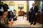 """President George W. Bush and Ezekiel """"Zeek"""" Taylor, 8, of Durham, N.C., the 2007 March of Dimes National Ambassador, pose for photographers during their meeting in the Oval Office at the White House Monday, July 30, 2007. White House photo by Eric Draper"""