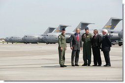 """President George W. Bush talks with Colonel Mark Bauknight, acting Commander of the 315th Airlift Wing, left, and Colonel John """"Red"""" Millander, USAF Commander of the 437th Airlift Wing, joined by Senator Lindsey Graham and Congressman Henry Brown, left, prior to observing cargo loading operations aboard a C-17 aircraft Tuesday, July 24, 2007, during a visit to Charleston AFB in Charleston, S.C. White House photo by Eric Draper"""